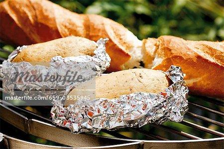 Pommes de terre et de la baguette sur la grille du barbecue