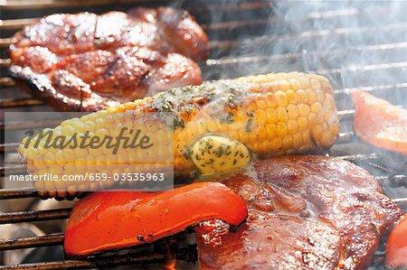 Maïs en épi avec beurre aux fines herbes, steaks de porc & poivre sur le barbecue