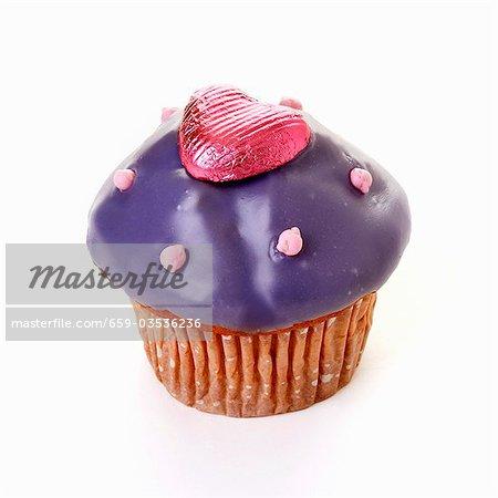 Muffin mit lila Vereisung und Schokolade Herz
