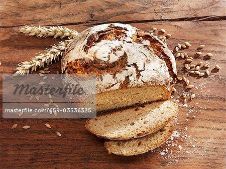 Rustique miche de pain, en partie en tranches, les oreilles & les grains de blé