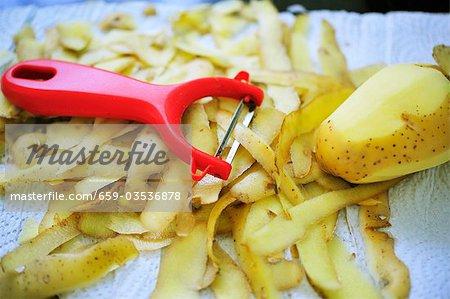 Sparschäler mit Kartoffelschalen und Kartoffel