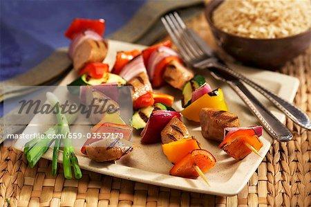 Saucisses grillées et brochettes de légumes sur une plaque. Fourchette et couteau