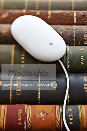 Gros plan d'une souris d'ordinateur sur cuir lié livres