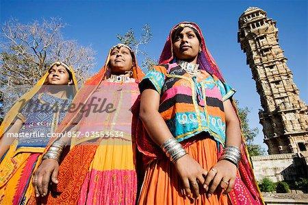 Three women standing near a fort, Vijay Stambha, Chittorgarh Fort, Chittorgarh, Rajasthan, India