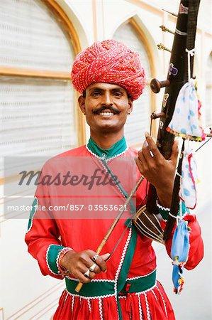 Mid adult man playing sarangi in a palace, City Palace, Jaipur, Rajasthan, India