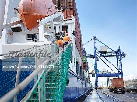 Marins regardant le chargement dans un conteneur de navire