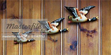 Three Decorative Ducks on Wood Panelling