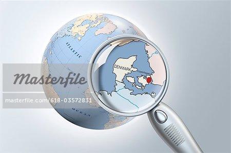 reading glass shows Denmark on a globe closeup