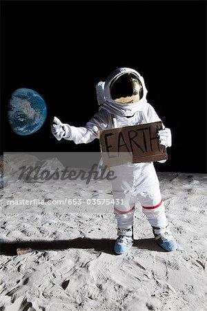 Un astronaute sur la lune avec son pouce, en tenant le signe de la « Terre »
