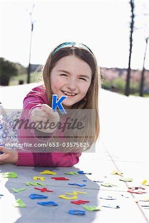 A girl holding a felt letter K