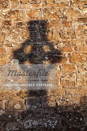 Schatten eines Kreuzes auf einer Steinmauer