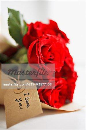 Nahaufnahme von roten Rosen mit Geschenk-tag