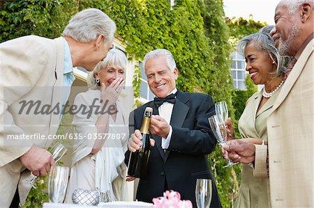 Senior gut gekleidete Paare Champagnerflasche öffnen
