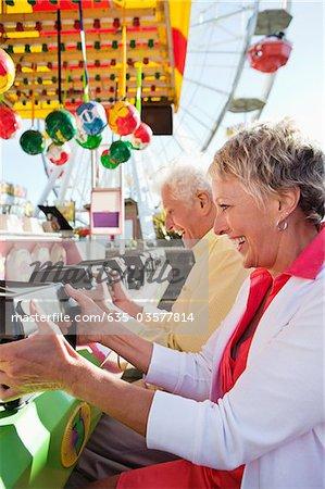 Senior couple jeu au parc d'attractions