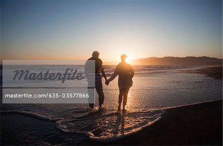 Tenue de couple Senior mains sur la plage au coucher du soleil