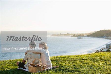 Altes Paar mit Picknick-Korb auf grasbewachsenen Hügel mit Blick auf Meer