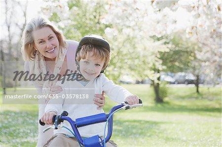 Souriant grand-mère petit-fils étreindre la bicyclette dans le parc