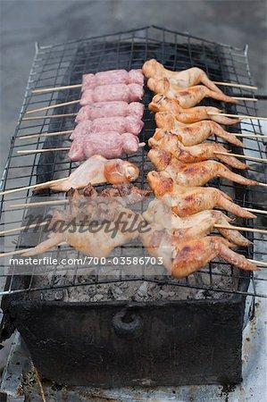 Gegrilltem Huhn und Wurst Kochen auf Holzkohle-Grill, Bangkok, Thailand