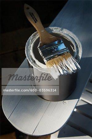 Pot de peinture d'apprêt blanche sur chaise Adirondack