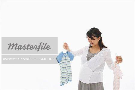 Enceinte femme Holding cintres des vêtements de bébé