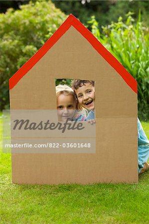 Boy und Girl Looking Out aus dem Karton Freisteller in Form eines Hauses
