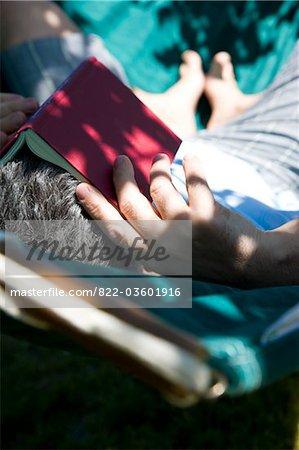 Homme sur hamac avec livre sur la tête