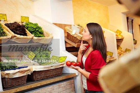 Adolescent dans un étal de fruits