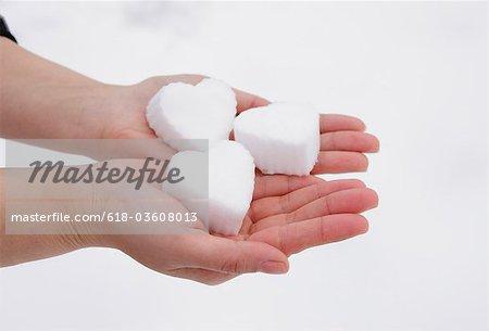Hands holding heart shaped snowball