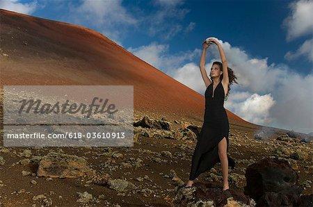 Jeune femme en robe noire, levant les bras au paysage désertique