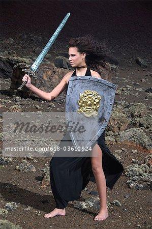Jeune femme en robe noire brandissant épée et son bouclier dans le paysage désertique