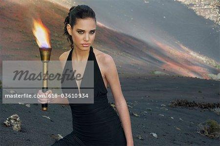 Portrait de jeune femme en robe noire tenant une torche enflammée dans le paysage désertique