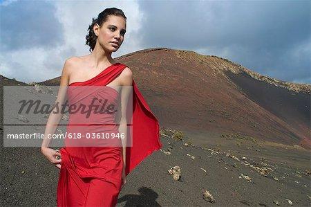 Jeune femme en robe rouge dans le paysage désertique