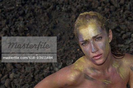 Portrait de jeune femme dans la peinture d'or corps contre le sol rocailleux