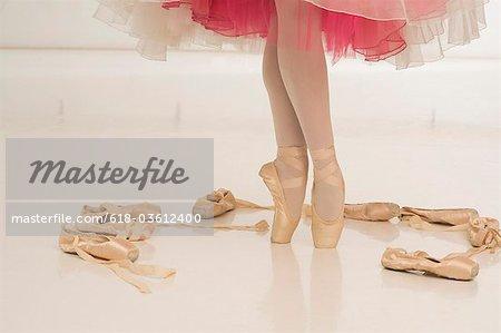 Une ballerine debout sur points entourés par des chaussures de ballet