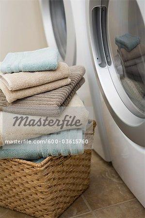 Pile de serviettes propres à côté de la laveuse et la sécheuse