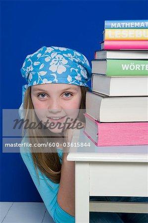 Jeune fille avec une pile de livres