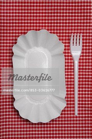 Bol et une fourchette en plastique sur une nappe à carreaux