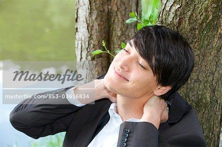 Jeune entrepreneur, appuyé contre le tronc d'arbre