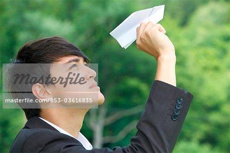 Homme d'affaires détenant jouet avion, profil