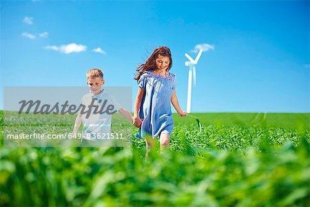 Wind turbine, boy and girl on field
