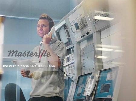 L'homme travaille au bureau de contrôle pour le plat satellite
