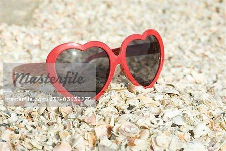 Heart-shaped sunglasses on beach