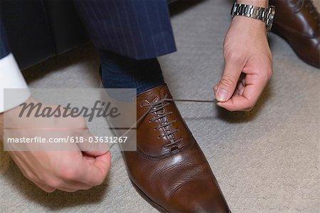 Un homme d'affaires relie un lacet de chaussure