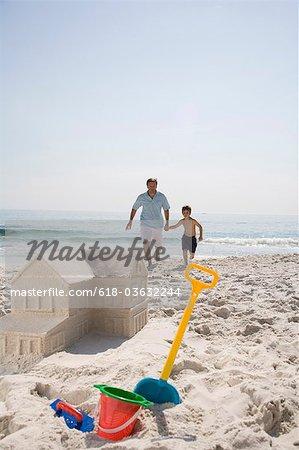 Père et fils en forme de château de sable de construction comme maison