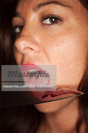 Frau leckt Blut aus einem Messer