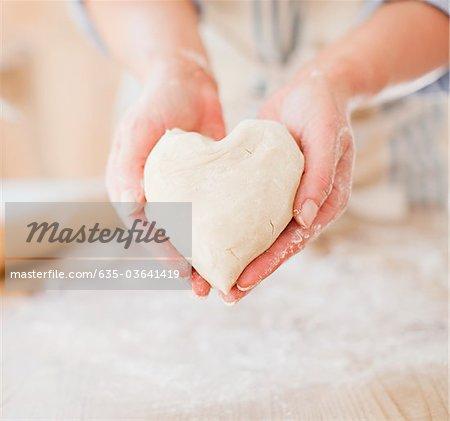 Close up of woman holding heart-shape dough