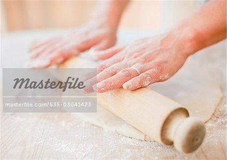 Teig mit Nudelholz auf der Küchentheke Rollen Frau hautnah