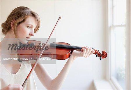Frau spielen Violine neben Fenster