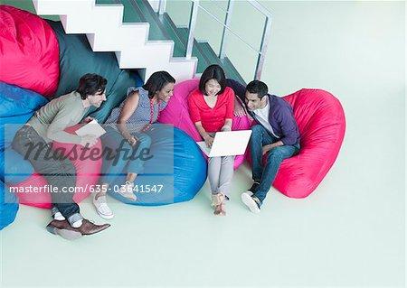 Geschäftsleute in Bohne Beutel Stühle, Blick auf laptop