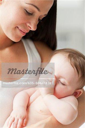 Gros plan d'une mère tenant le bébé qui dort sucer le pouce